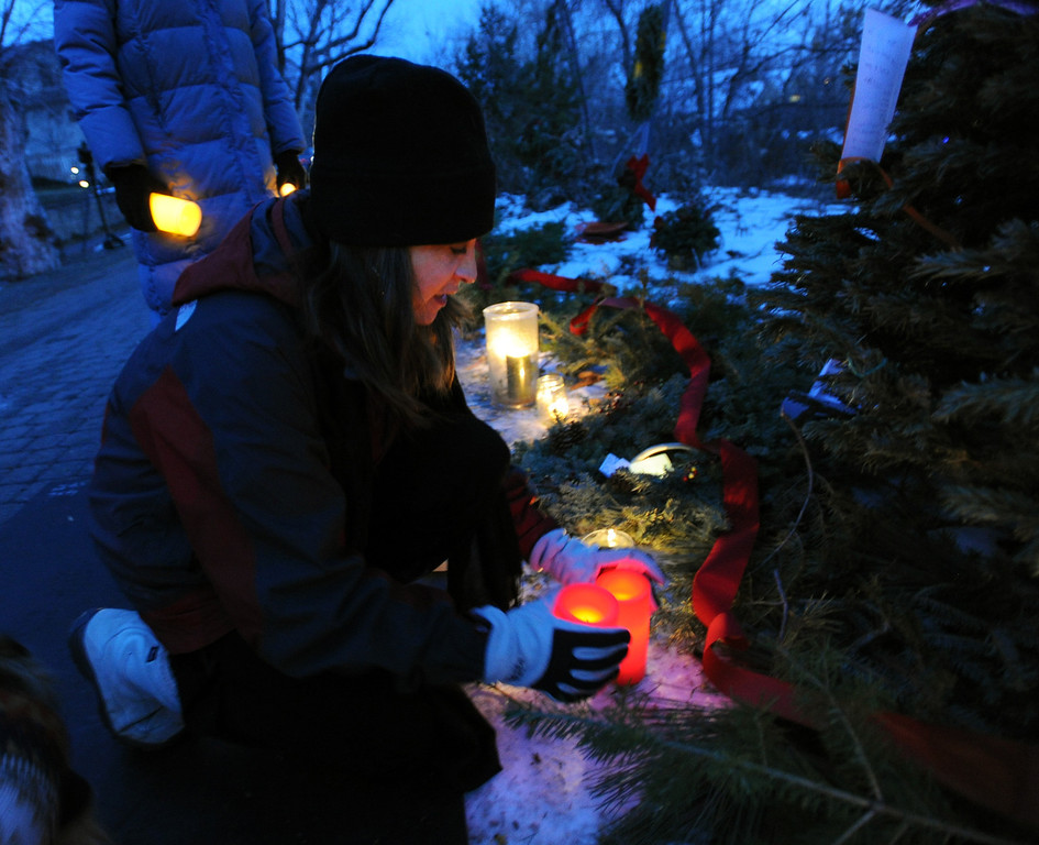 "Beth Humphrey puts down candles at the elk memorial tree.<br /> Jim Riemersma was among Mapleton Hill residents holding a candlelight vigil Sunday evening, celebrating the life of the fallen elk.<br /> For a video and more photos of the vigil, go to  <a href=""http://www.dailycamera.com"">http://www.dailycamera.com</a>.<br /> Cliff Grassmick  / January 6, 2013"