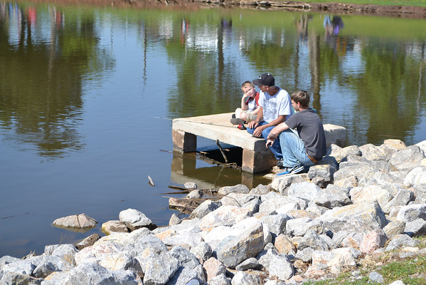 Landen Cook (left) learns the art of waiting as he fishes with Anthony Couch (center) and his son, Anthony Couch Jr.