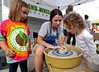 Elizabeth Lee, Hand and Wheel Pottery, throws a small pot under the watchful eyes of Zoey Moskowski, left, and Elena Lee at the Essence of Ambler Fashion Show Friday, Sept 5, 2014. <br /> Montgomery Media staff photo by Bob Raines