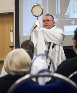 During adoration Bishop David Talley holds the Blessed Sacrament before the room of attendees in the American Sign Language Track.  (Photo by Thomas Spink / Archdiocese of Atlanta)