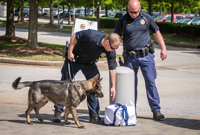 Lt. Hensley, bending over, and Officer Sobczak check out an unattended bag outside the convention center with K-9 Adam.  (Photo by Thomas Spink / Archdiocese of Atlanta)