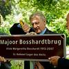 De heer Kuiper van de gemeente Amstelveen en de heer Dijkstra assisteren wethouder Levie bij het opschroeven van de nieuwe naamplaat aam de andere kant van de brug.
