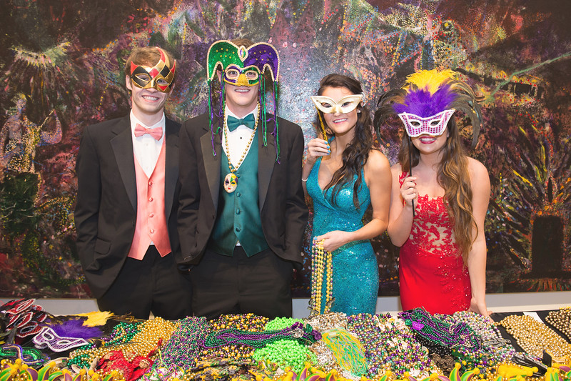 Student volunteers (ambassadors?) assist with passing out mardi gra themed decor for the 2015 Annual President's Ball.
