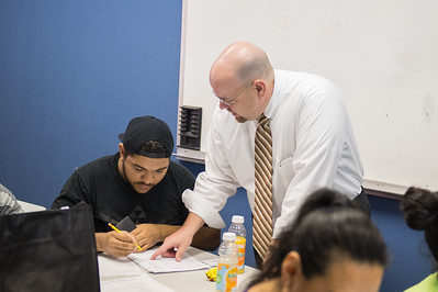 Jordan Vonchampion is assisted by Scott Kruse during the Financial Literacy class held at Coastal Compass in partnership with TAMU-CC College of Business.