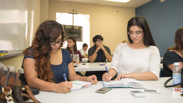 Diamond Escobar(left) and Audrey Rivera take notes during the Financial Literacy class held in Coastal Compass in partnership with TAMU-CC College of Business.