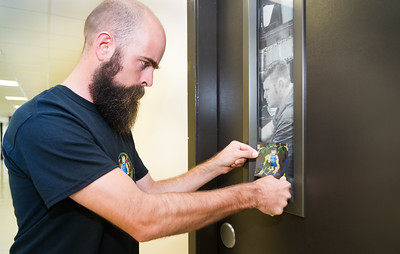Student veteran Kyle Bauer demonstrates the use of Green Zone stickers. The Green Zone sticker placed on doors indicates to students which facultiy and staff are Green Zone certified to aid veteran students during transitioning periods and/or anytime of need