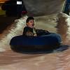 Isaak Jordan Gloria rides an inner tube down the ice slide during Islander Lights.
