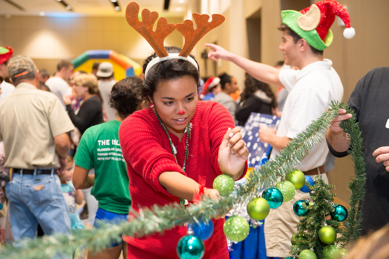 Andrea Gilson attempts to place as many ornaments on the garland without using her hands.