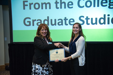 graduate student Alora Korb recieves her award for presenting her 3 minute thesis