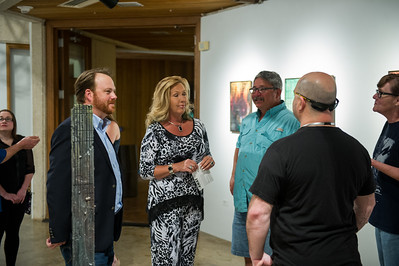 The artist Pual Seeman talks with a group of attendees of his show