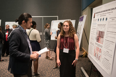 Judge Robert Fuentes reviews Courtney Knauer's poster during the McNair Scholarship Poster presentation.