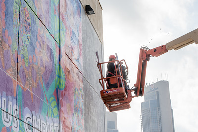 Sandra Gonzalez operates the boom lift as she prepares to add the final panels for the Corpus Christi - Mural. Located on the side of the Corpus Christi - Caller Times building. Thursday June 16, 2016.
