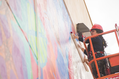 Sandra Gonzalez rolls out painted clothing panels on the Corpus Christi Mural. Thursday June 16, 2016.