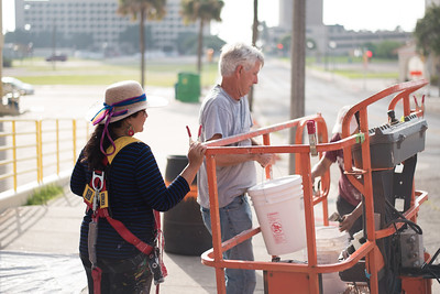 Earl Parr assists Sandra Gonzalez with one of many buckets of acrylic palmer used for the Corpus Christi-Caller Times mural.