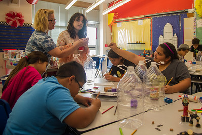 Teachers help students of wrting camp to create ther own robots.
