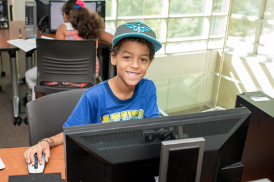 Zamar Wisner pauses for a photo while working on his assignment for the Young Writers Camp.