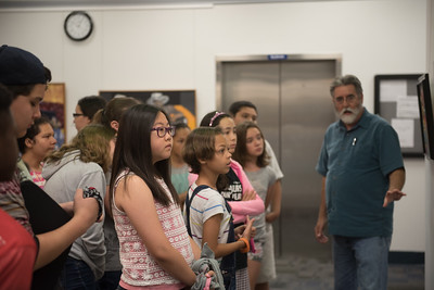 Jeffrey Janko goes over the art work displayed at the Islander Faculty and Staff Art Exhibition. During the young Writers Camp tour of the Mary and Jeff Bell Library.