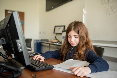 Ava Garcia works on typing her notes on the computer during the young writers camp.