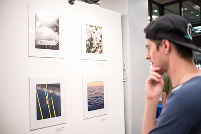 Student Eli Berke observes the photographs displayed at the Islander Phone Photography Show.