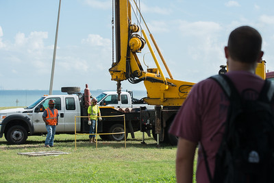Geology students observe from a distance as workers prepare to dig water well sample sites.