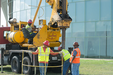 Workers prepare the dig sight for the geology departments water wells in front of the PAC.