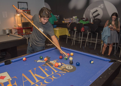 Student Joseph Hernandez playing pool at the Comm Club mixer.