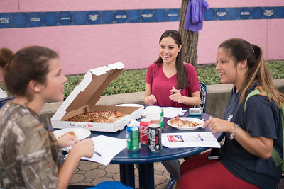 Students Melody Gartner (left), Susana Valdivia and Alyssa Olivares enjoy pizza as they fill out a survey during the Register to Vote event in the Hector P. Garcia Plaza.