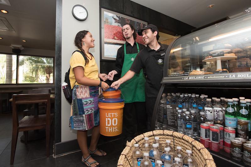 Melissa Zamora (left) receives coffee grounds from starbucks baristas Juan Zapeda and Dylon Garrett.