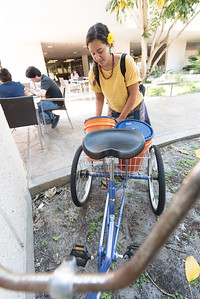 Melissa Zamora with Islander Green, places used coffee grounds from Starbucks into her tricycle.
