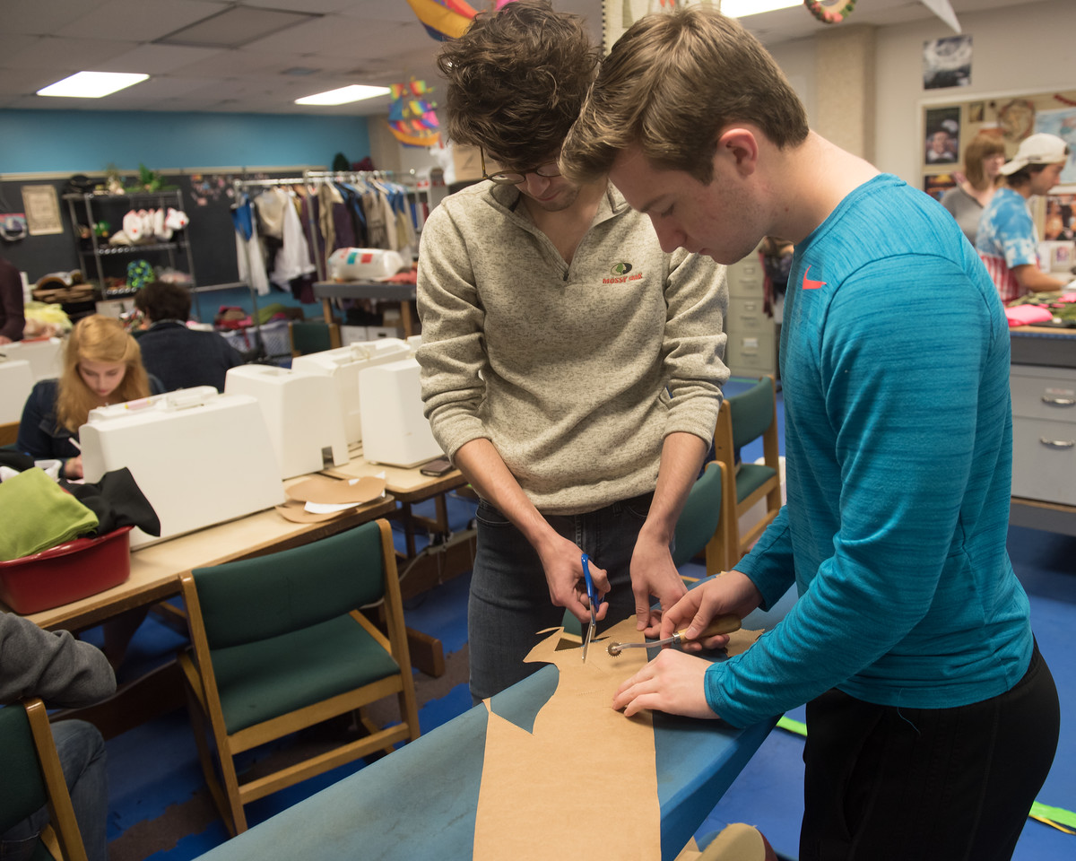 Iran Froese and Austin Klopfenstein cut cloth for a monkey hat to be presented to kids at Driscoll Children's  Hospital