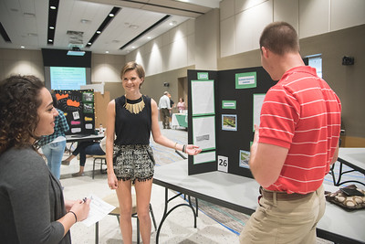 Morgan McCutchen and Daneil Green present their project to student Stephanie Cantu during the Green Campus Poster Fair.