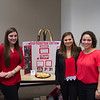 Students (left to right) Erin Longoria, Cyntha Stewart and Emily King next to their presentation for the Ronald McDonald House.
