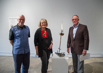 "Freg Reuter With Linda and Robert Pate standing next to the piece ""Invasive Species""."