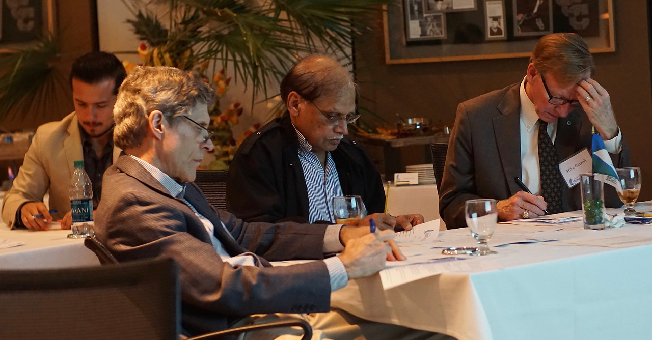 Jim Shiner (left),  Govind Nadkami,  and Mike Carrell vote after watching video submissions during the Buc Days Ideas Challenge.