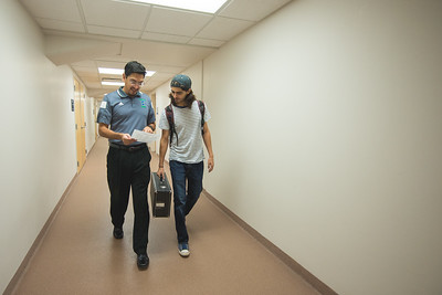 Dr. Kenneth Iyescas and Jordan Gonzalez go over a schedule as they head to the music department.