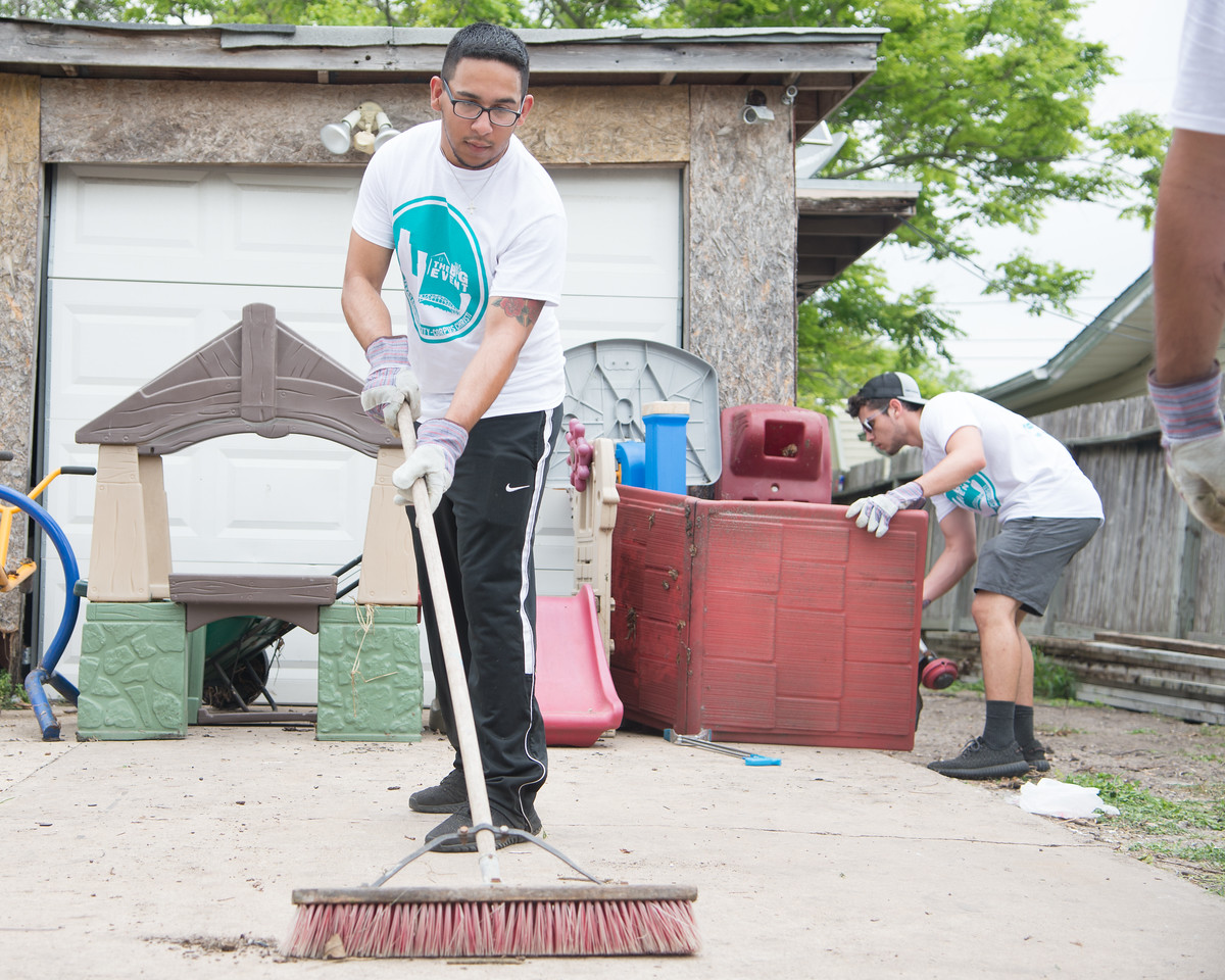 Student volunteer Marco Granciani sweeping a driveway during The Big Event.