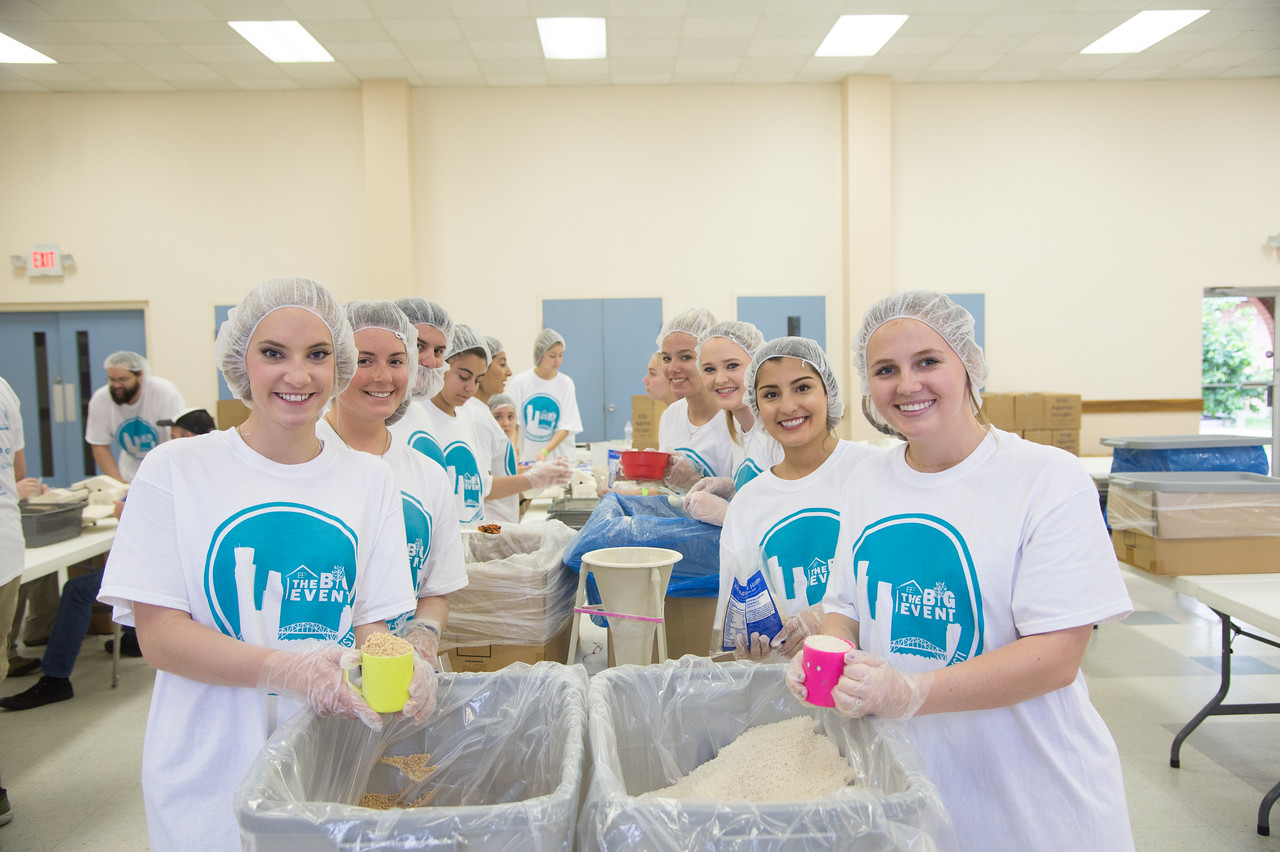 "Students smile for our cameras while performing volunteer work in the community for Student Volunteer Connection's ""Big Event""."