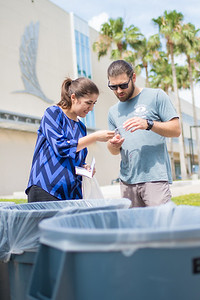 Megan Greige (left) shows  Ben Ireland a demonstration on how to properly sort your recyclables.