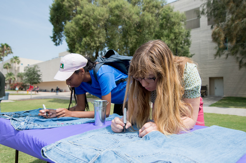 Olivia Whitehurt (left) and Mia Greene write a positive message on a pair of jeans during the Denim Day event on the East Lawn.