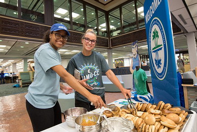 Dominique Casey (left) and Olivia Cohoon enjoy complimentary bagels and school supplies provided by the Islander Alumni Association during Finals Week.