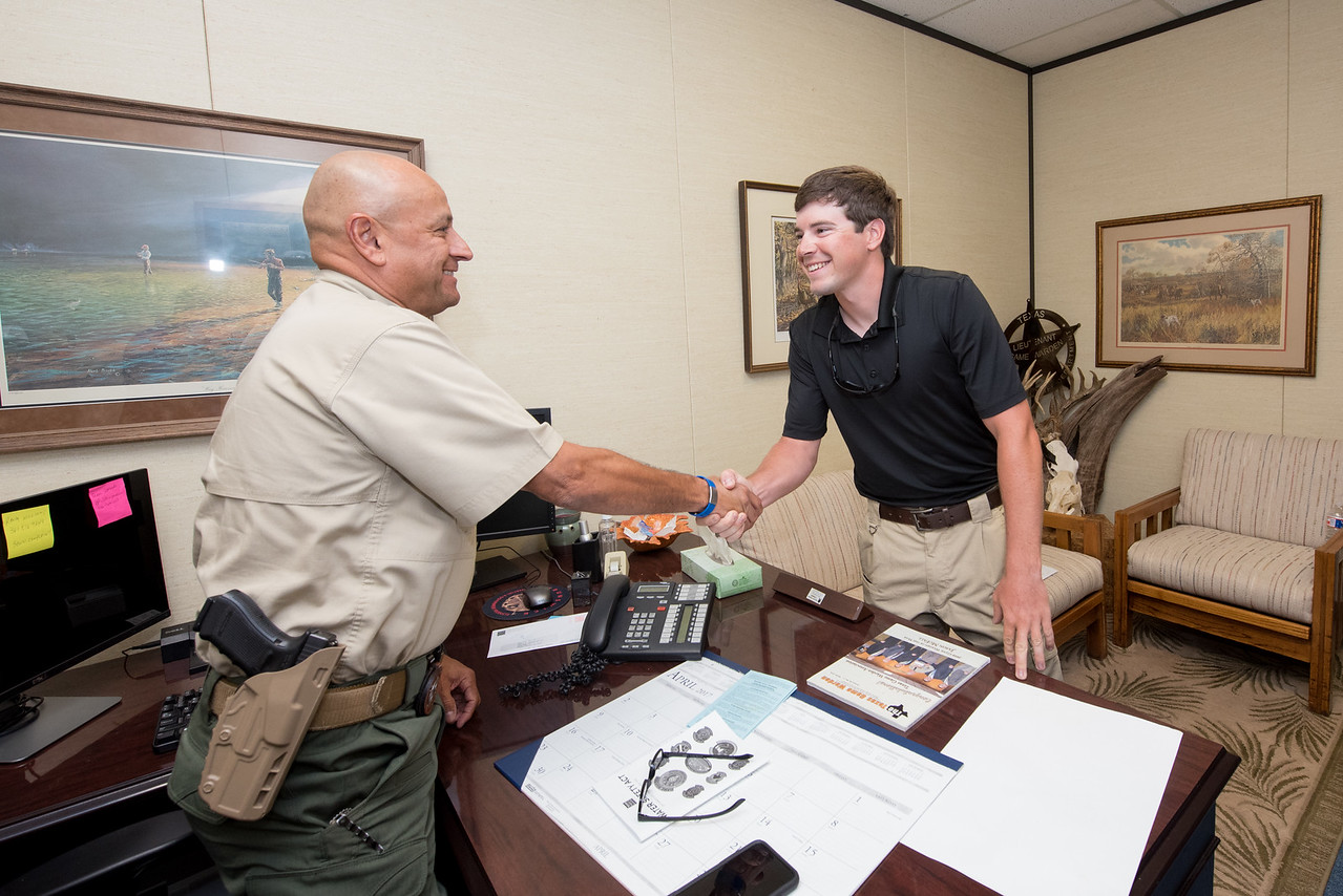 Captain Marvin Tamez (left) speaks with student intern Reid Dungan as he prepares for his ride-along with a Texas Parks and Wildlife game warden.