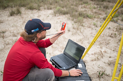 Alistair Lord uses an anemometer to get wind speed measurements as he initializes the LIDAR system.