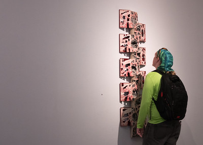 A student inspects a piece by Brian Dettmer in the Weil Gallery.