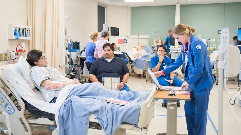 Nursing student Lauren Ritchie (far right) looks over the charts of her patient during a Transitions Simulation.