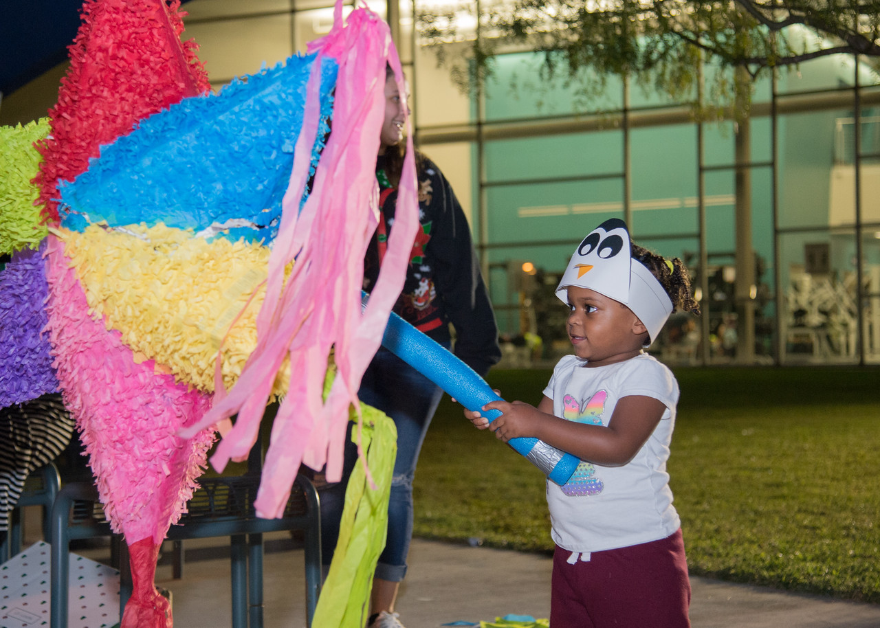 Neriah Colvin (2) hits a pinata during the Islander Lights Celebration.