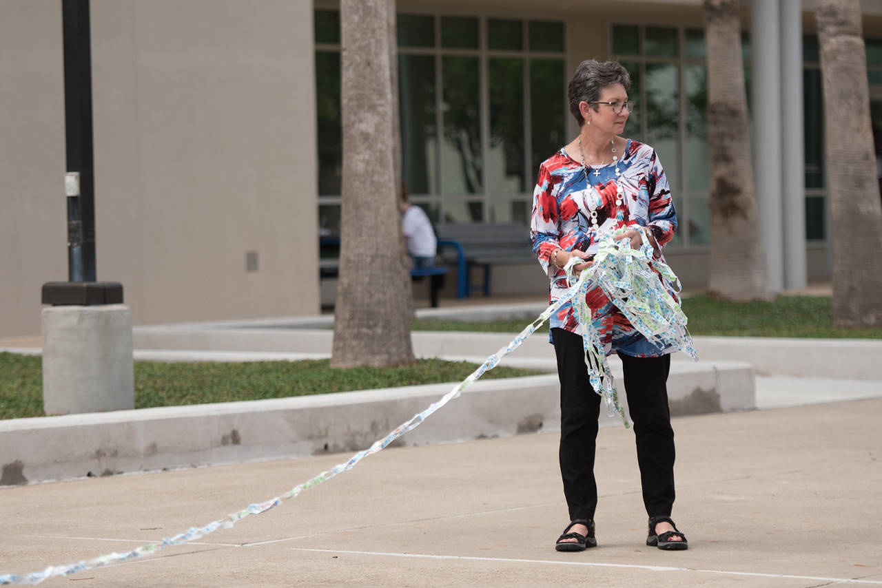 Dr. Pamela Greene unravels a collection of links to be stretched from the anchor in front of the University Center to the Dugan Wellness Center.