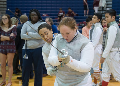 Nia Lane (Left) helps Savannah Stilwell (right) with her fencing equipment.