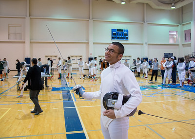Nickodemus Guerra striking a quick pose before beginning a match at the fencing tournament.