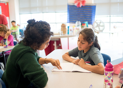 Olivia Ramos (left) helps elementary school student Kylie Escochea with her writing during the Summer Writing Camp.