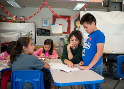Elementary school student Lawrence Zheng receives help from Olivia Ramos during the Summer Writing Camp.